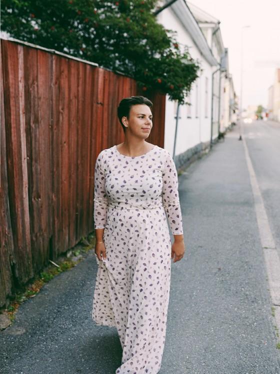 Woman in white summer dress walking down the streets in Kokkola