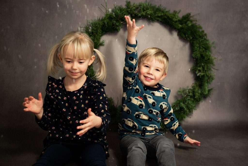 Girl and boy throwing fake snow in the air