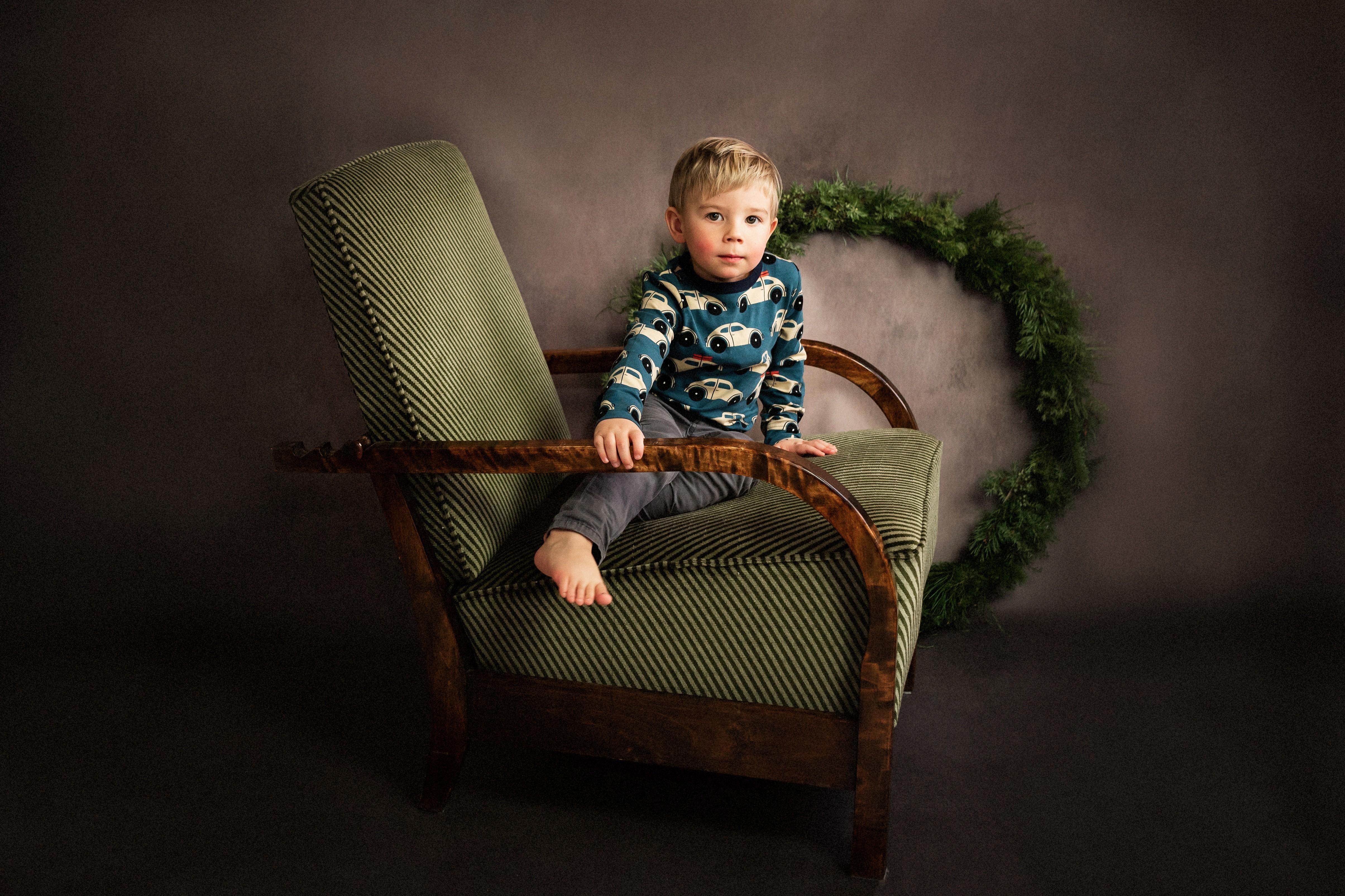 Studio portrait of boy sitting in chair