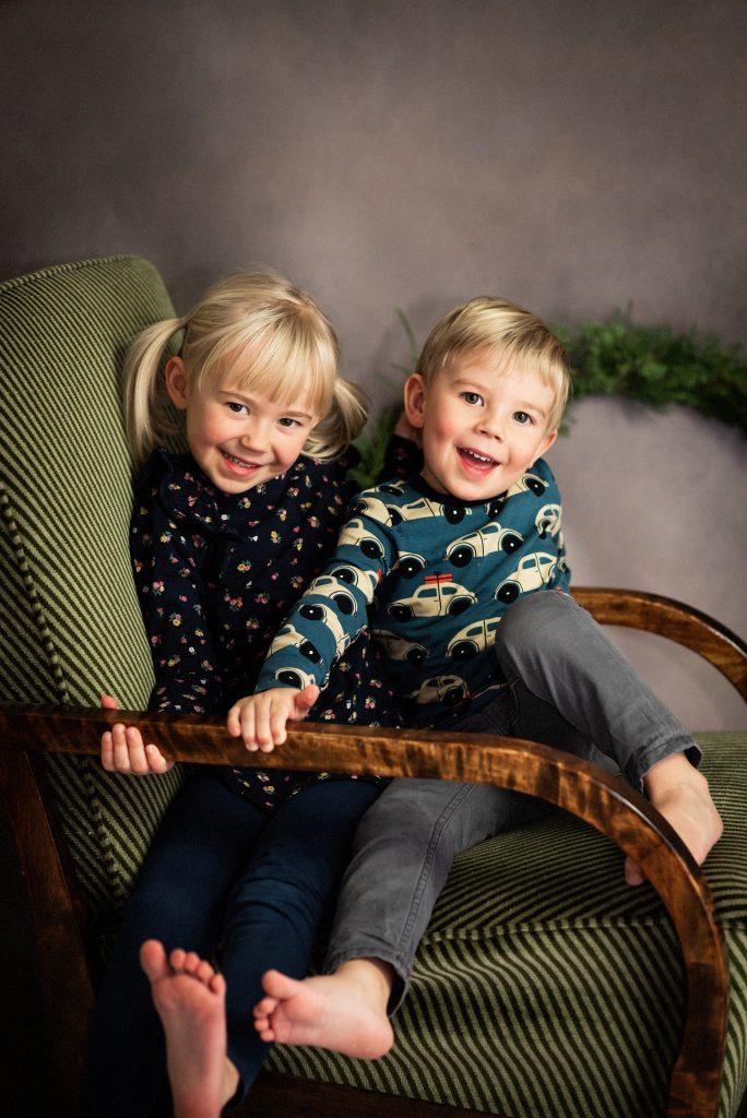 Studio portrait of siblings in armchair